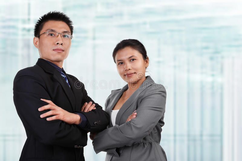 Two Asian business people pose. Together with blur glass windows as background stock photo
