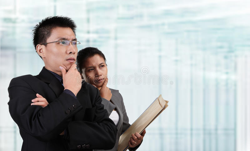 Two Asian business people thinking. And looking to empty space with blur glass window background stock photo
