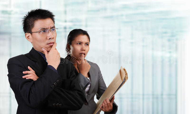 Two Asian business people thinking. And looking to empty space with blur glass window background. **** PS: stitching the length of background to fit for banner stock photos