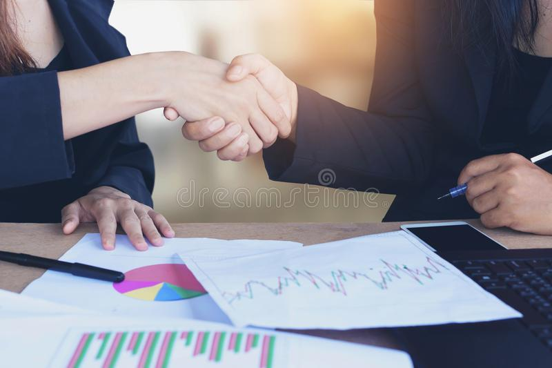 Two Asian business woman handshake after working together and agree on their project at office with some financial paper. Graph on desk ,teamwork and successful stock images