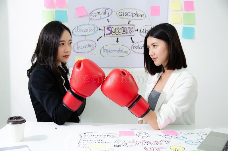 Two asian business women fight. Angry women, looking at each other with hatred, blaming for problem. Friendship difficulties, stock photo