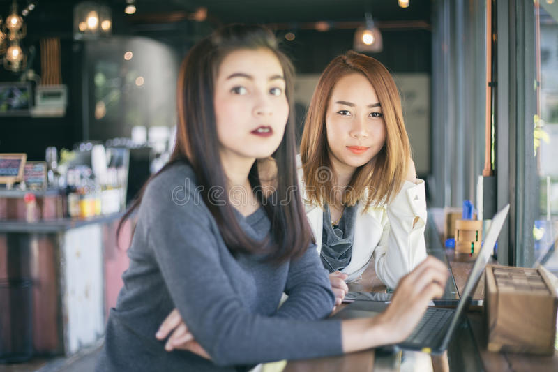 Two Asian business women using notebook working and Discussion o royalty free stock images