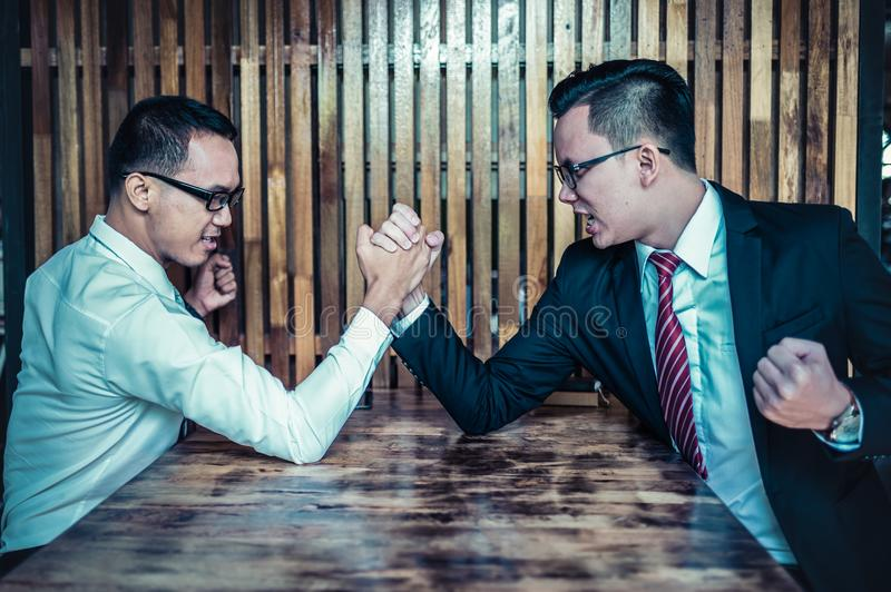 Two Asian businessman expressed a serious expression and fighting by used arm wrestling on wood table. Concept of business competition stock photo