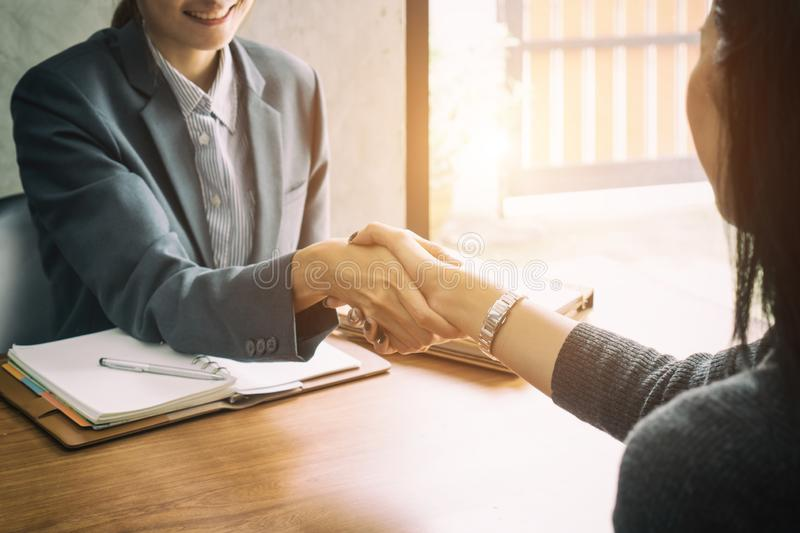 Two Asian businesswomen shaking hands over a desk as they close a deal or partnership, focus to hands of young Asian lady royalty free stock image