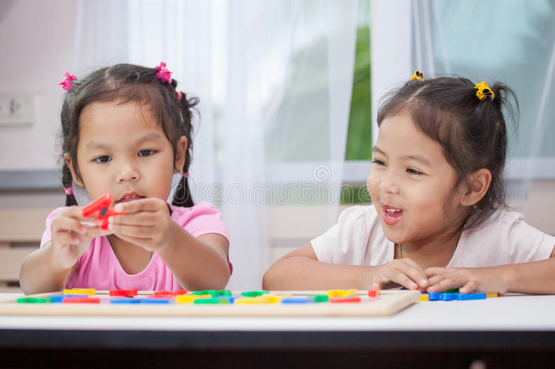 Two asian child girls having fun to play and learn magnetic alphabet. Two cute asian child girls having fun to play and learn magnetic alphabets together stock photos