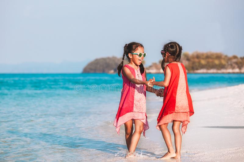 Two asian child girls holding hand each other and playing together on beach near the sea in summer vacation. Two cute asian child girls holding hand each other stock photography