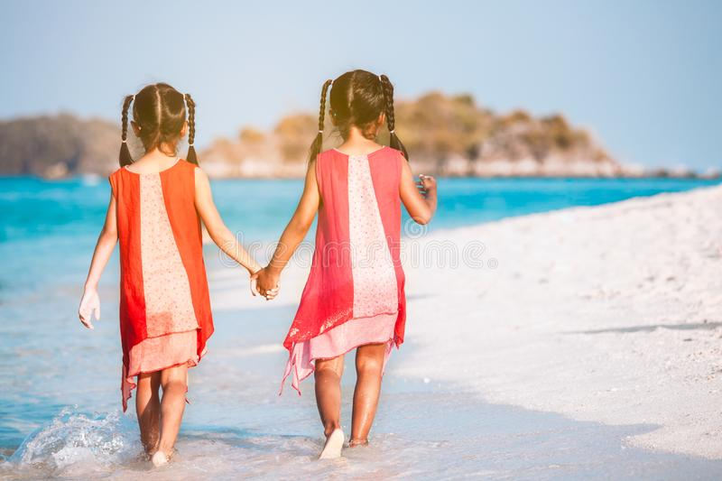 Two asian child girls holding hand each other and walking together on beach near the sea in summer vacation. Two cute asian child girls holding hand each other royalty free stock photos