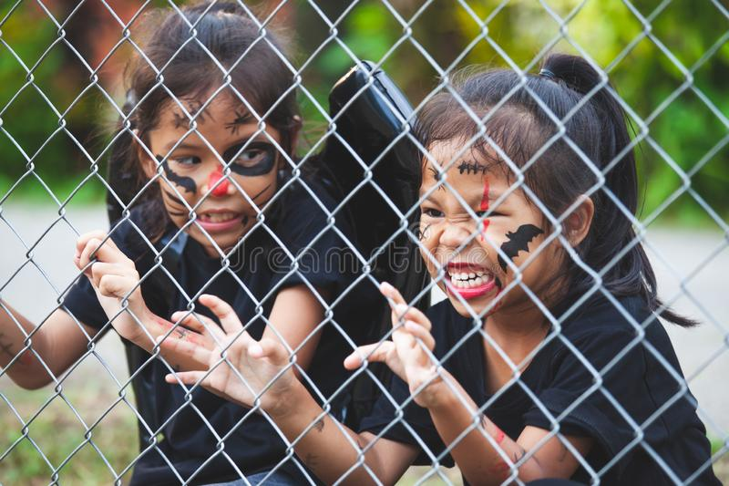 Two asian child girls wearing halloween costumes and makeup holding steel mesh and  having fun on Halloween celebration stock images