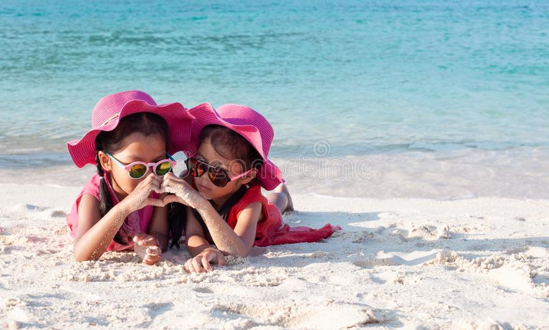 Two asian child girls wearing pink hat and sunglasses playing with sand and making hand heart shape together on the beach. Two cute asian child girls wearing royalty free stock photos