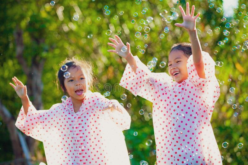 Two asian child girls wearing raincoat having fun to play with bubbles together after rainy. Two asian child girls wearing raincoat having fun to play with stock photo