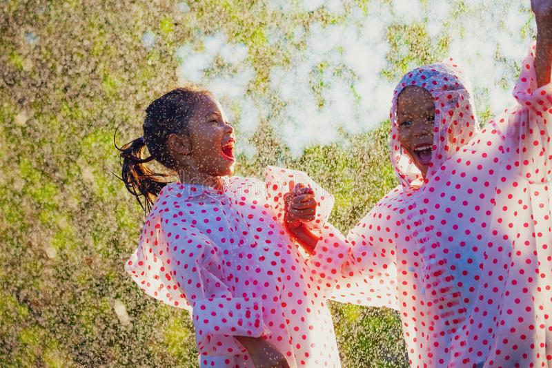 Two asian child girls wearing raincoat having fun to play with the rain together. In the sunlight royalty free stock images