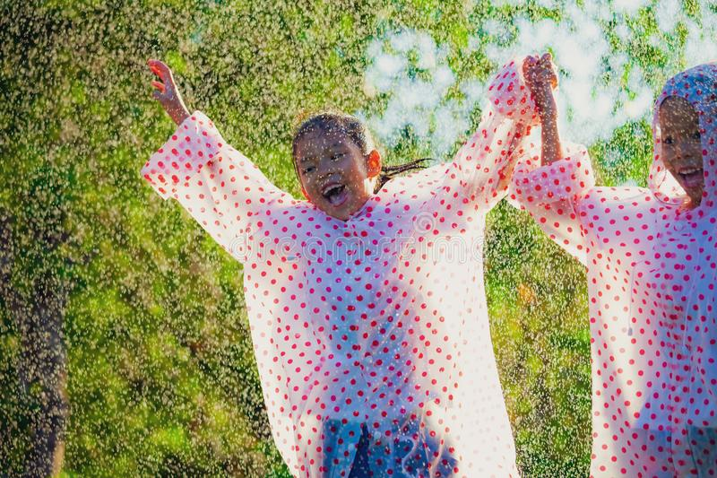 Two asian child girls wearing raincoat having fun to play with the rain together. In the sunlight stock photos