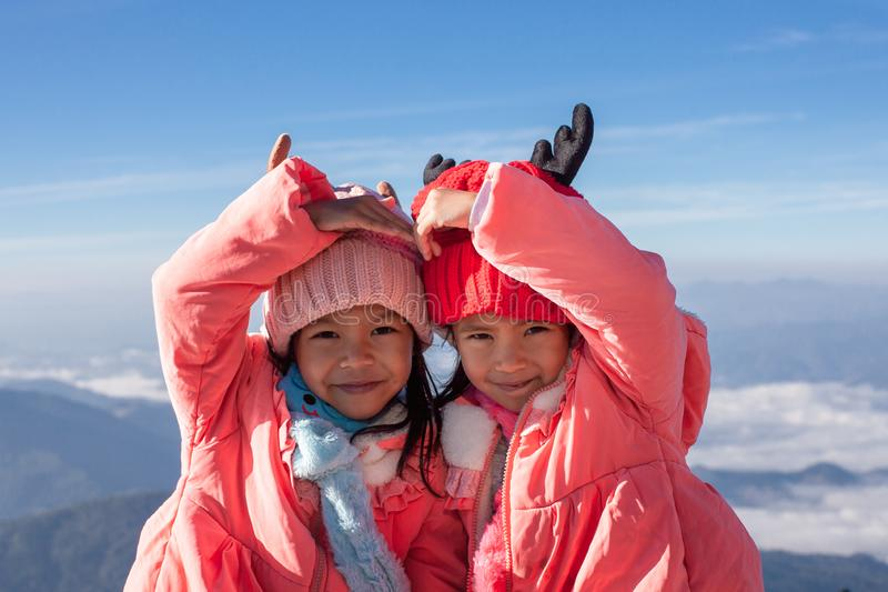 Two asian child girls wearing sweater and warm hat making heart together with love at the beautiful mist and mountain royalty free stock photos