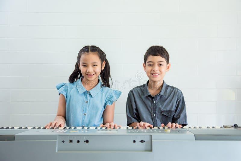 Children playing music keyboard at music school stock photo