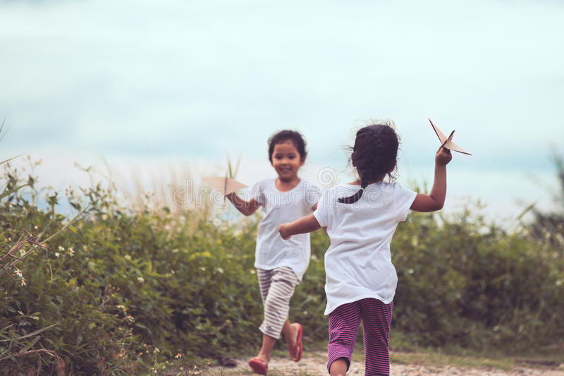 Two asian children playing with toy paper airplane. In the meadow together in vintage color tone stock photo
