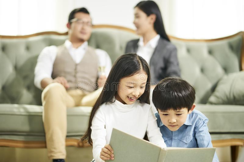 Two asian children reading book together stock photography