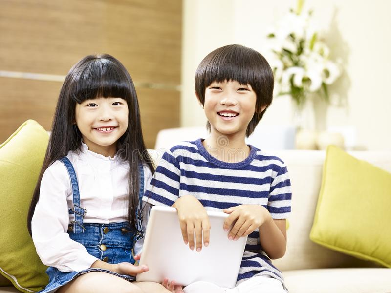 Two asian children sitting on couch looking at camera smiling. Two cute asian children little boy and little girl sitting on couch holding digital tablet looking royalty free stock image