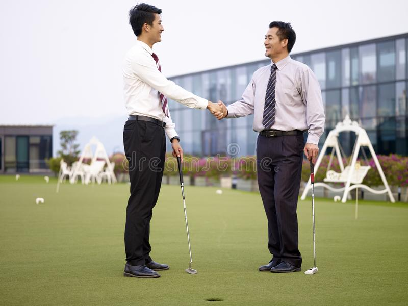 Two asian corporate executives shaking hands on golf course stock photos