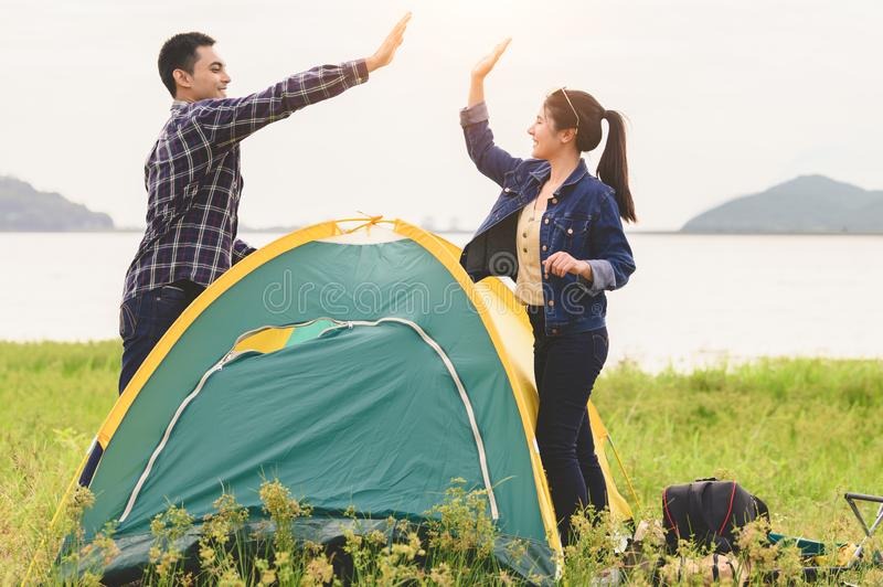 Two Asian couples finished pitch and doing high five for stay in camping tent  meadow overnight honeymoon picnic. People lifestyle stock images