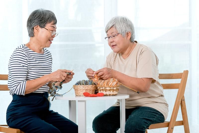 Two Asian elderly woman sit on chair and have activity of knitting, also talk together with smile in front of balcony. Two Asian elderly women sit on chair and stock photography