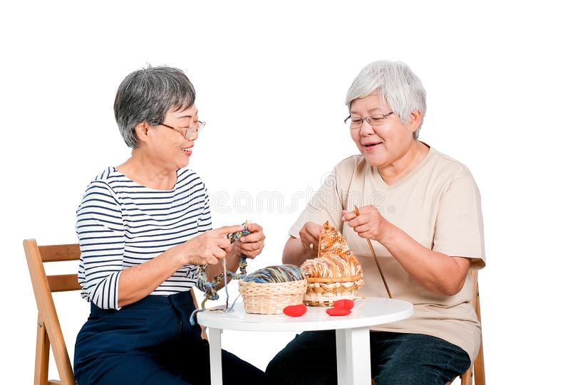 Two Asian elderly woman sit on chair and have activity of knitting, also talk together with smile in front of white background. Two Asian elderly women sit on stock image