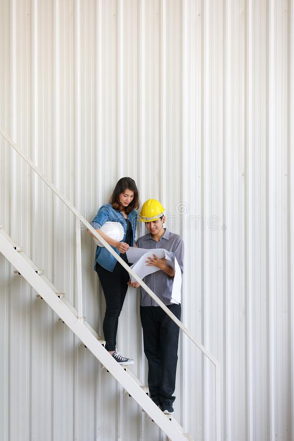 Two Asian engineers, man and woman, discussing in construction site stock photography