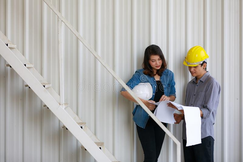 Two Asian engineers, man and woman, discussing in construction site royalty free stock photo