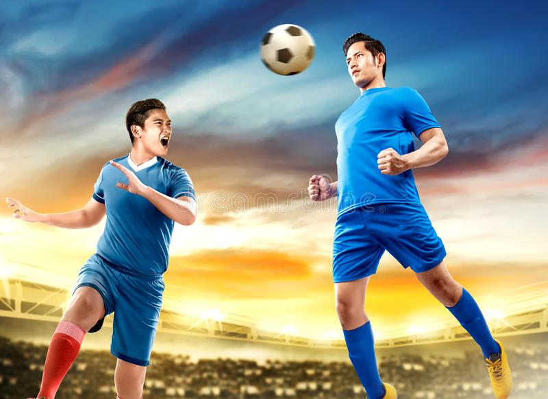 Two asian football player man jump in the air and duel heading the ball. Two asian football player men jump in the air and duel heading the ball on football stock images