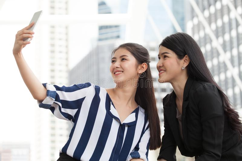 Two asian girls friends taking selfie photo with smartphone in urban city stock images