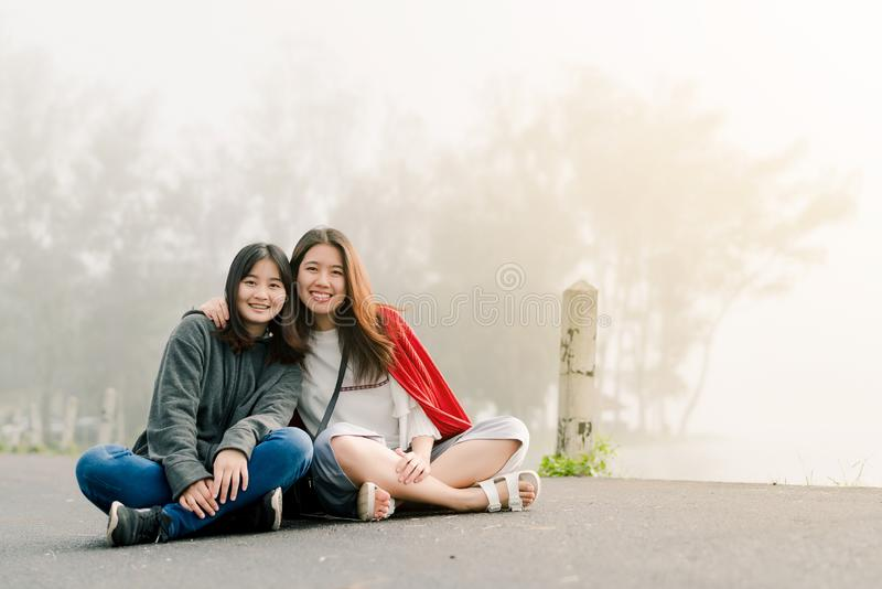 Two asian girls Very close friends Wearing a sweater In tourist attractions Along the road beside the reservoir in the thick fog. With a smiling expression of stock images
