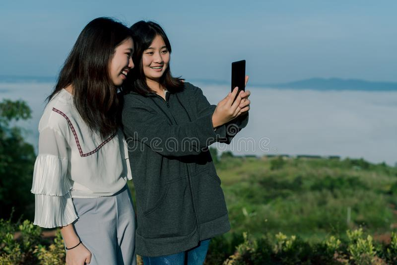 Two Asian girls wearing a sweater, take a selfie phone, take pictures in the tourist area behind the fog and mountains with a. Smiling expression of happiness stock photo