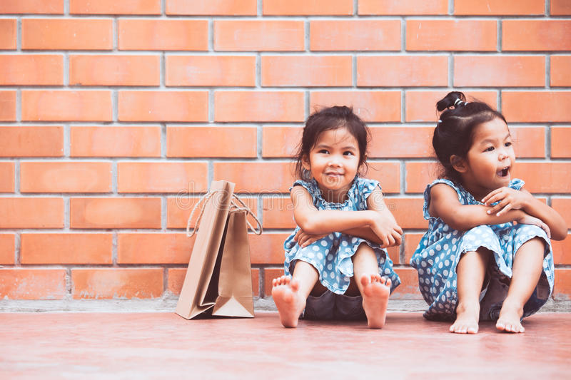 Two Asian girls who feel bored sitting and hugging their knees. On the floor while waiting for their parents to shop on the wall of the masonry walls in antique stock photos