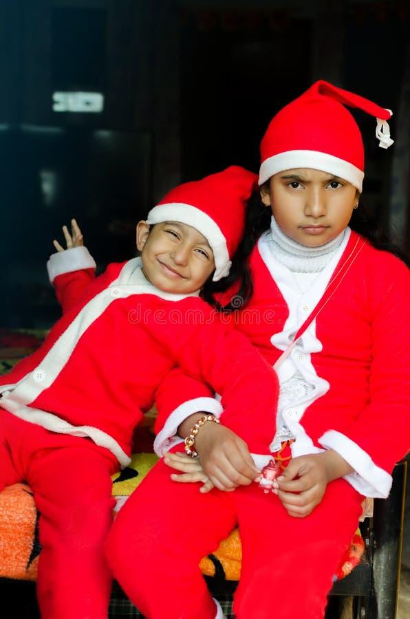 Two Asian Indian Ethnicity kids wearing Santa Hat waving having royalty free stock photography