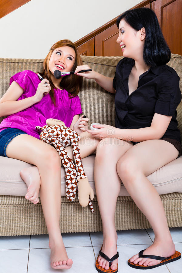 Two asian indonesian girls home using make up stock images