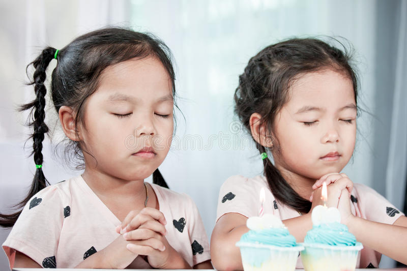 Two asian little child girls make folded hand to wish. The good things for their birthday in party stock image
