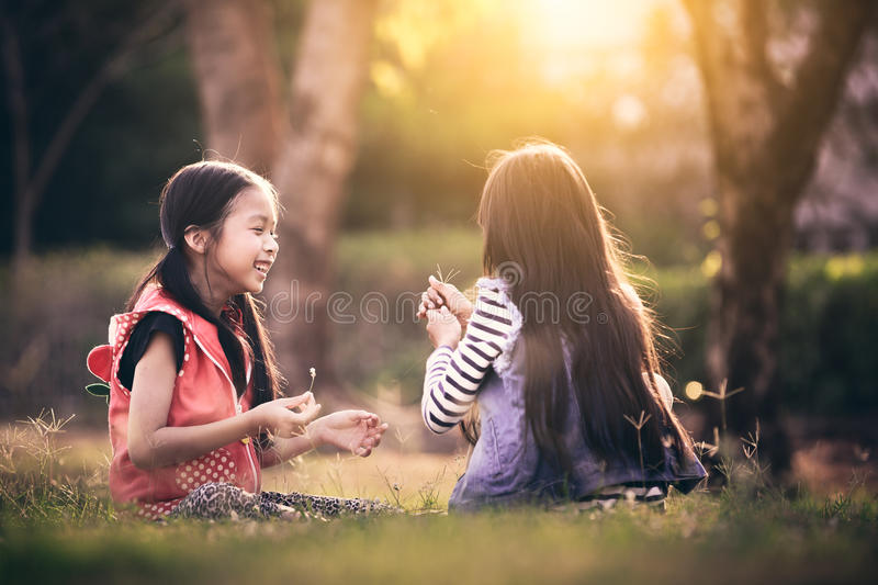 Two asian little girl. Playing together in a park with sunset stock photos