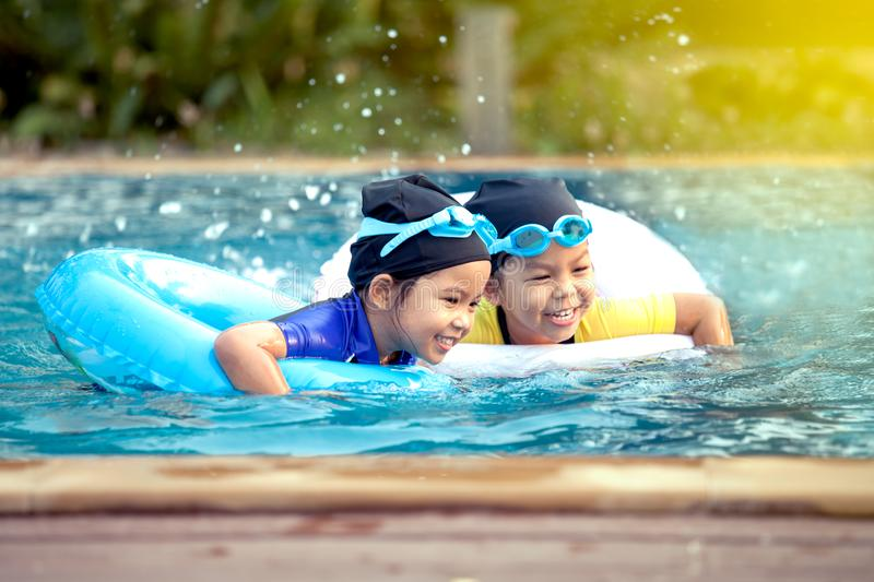 Two asian little girls having fun to swim in swimming pool stock photos