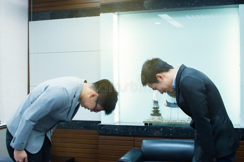 Two business bowing each others for business manner. Two asian men bowing for business manner after dealing agreement royalty free stock image