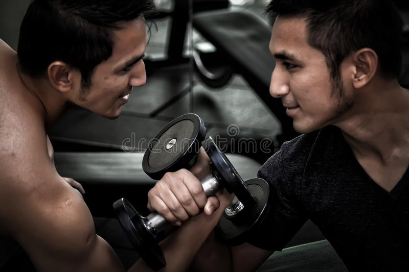 Two Asian men use dumbbell exercise weight-lifting arm-wrestle c. Ompete in fitness gym stock photo
