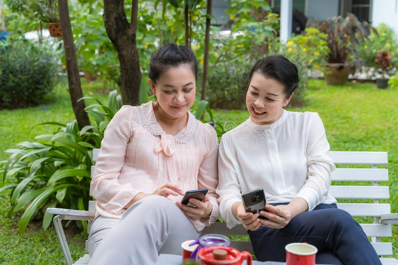 Two Asian middle-aged women who are friends are looking at the phone stock photography