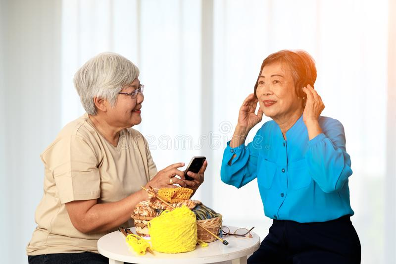 Two Asian 70s seniors enjoy activity together in living room with white curtain stock image