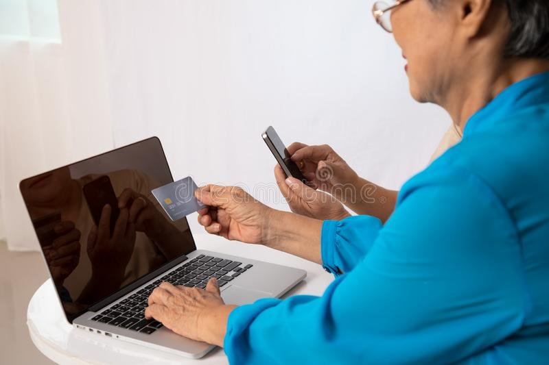 Two Asian senior women check online shopping from laptop stock images