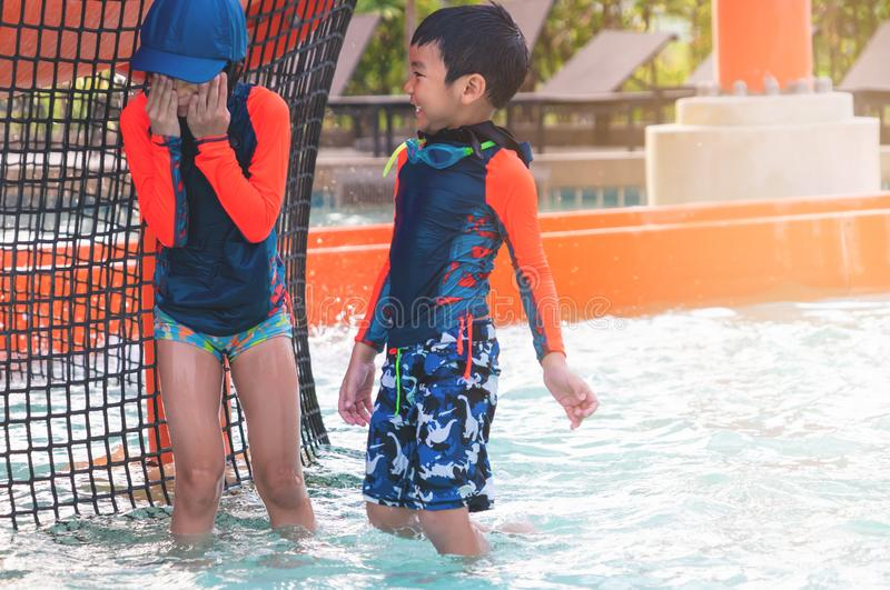 Two siblings in playing together in Water Aqua park pool royalty free stock photography