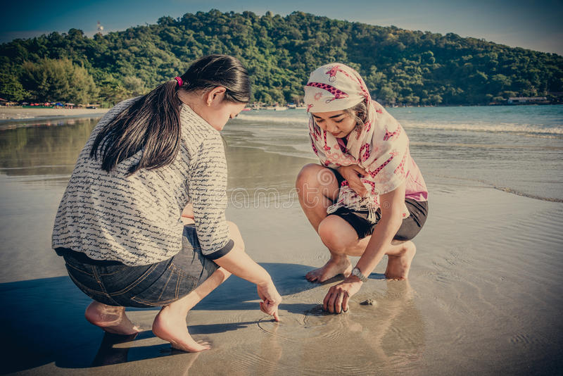 Two Asian Thai girls are digging to find shell on the beach. Two Asian Thai girls are digging the sand to find shell on the beach coast of Rayong, Thailand in royalty free stock image
