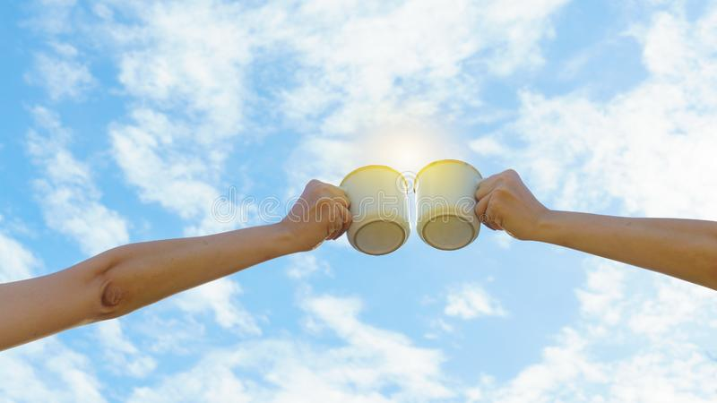 Two Asian woman hands clink hot coffee mug outdoor in the morning. Friends enjoy drinking coffee together. Clear sky background. Copy space royalty free stock image