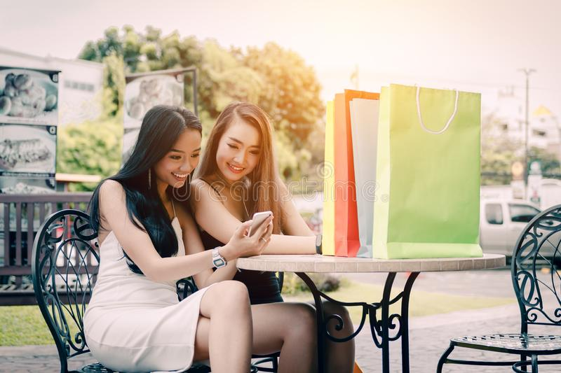 Two asian woman sitting at store cafe and watching smartphone at stock images