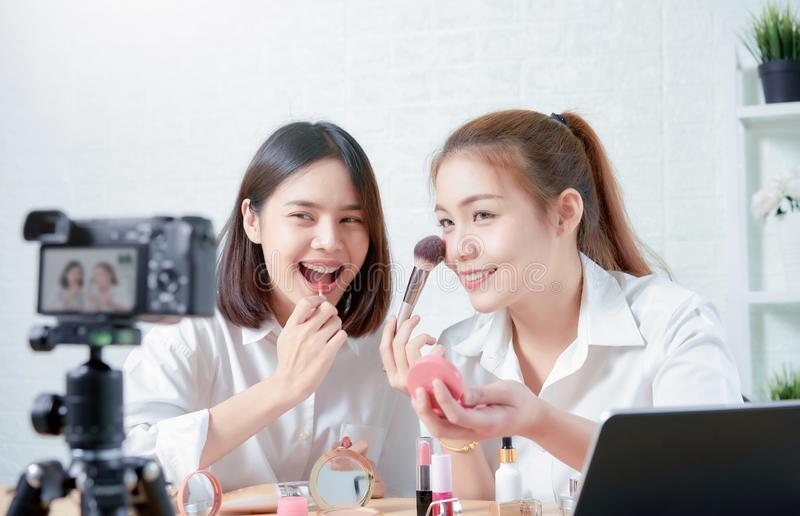 Two asian women beauty vlogger video online is showing make up on cosmetics products and live video on digital camera. royalty free stock images