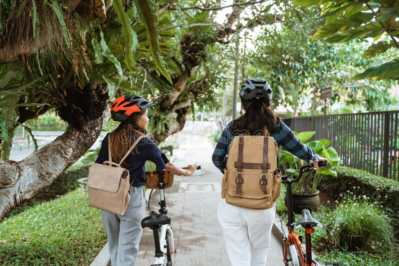 Two Asian women chatting and walking while walks with folding bikes stock photos
