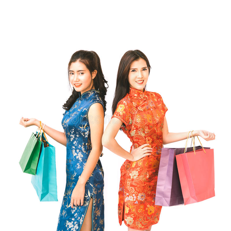 Two Asian women in Chinese qipao traditional dress holding shopping bags, Chinese new year or shopaholic girls concept. Isolated on white background royalty free stock photography