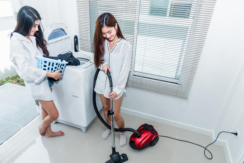 Two Asian women doing housework and chores in kitchen. Indoors activity and Lifestyles concept. Beauty lesbian theme royalty free stock photography